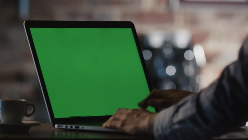 Man using Laptop with Green Screen in Cafe. Shot on RED Cinema Camera in 4K (UHD).