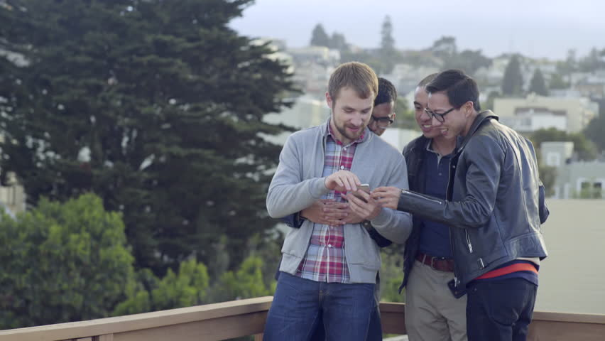 Group Of Gay Men Look Through Their Friend's Smart Phone Pics At A Party In San Francisco (4K)