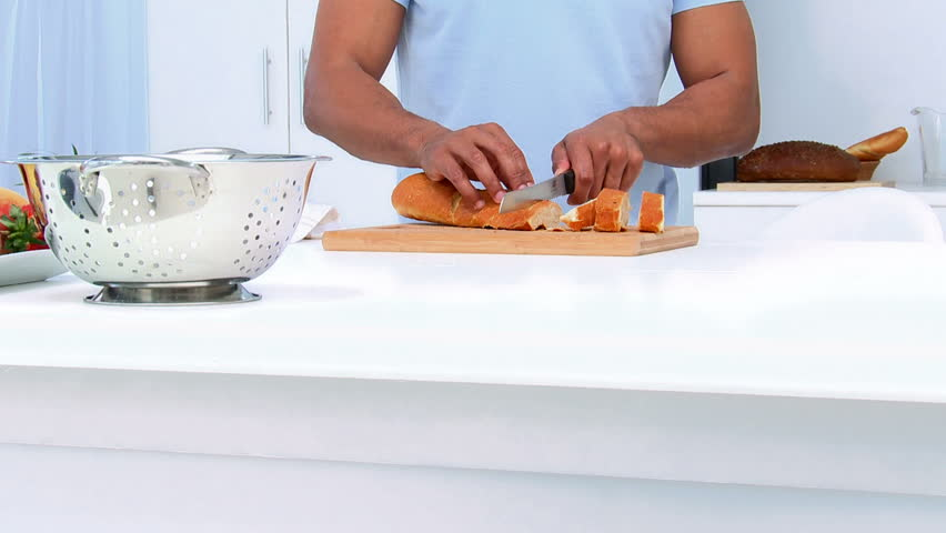 Handsome man cutting bread in the kitchen  - HD stock video clip