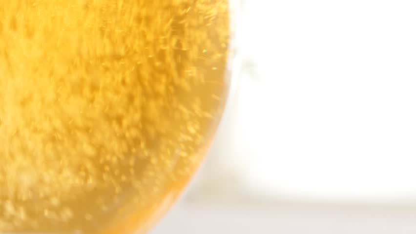 Filling to the top glass of  beer while slow tilting 4K 2160p UltraHD footage - Golden beer color bubbles and foam in the glass 4K 3840X2160 UHD video - 4K stock video clip