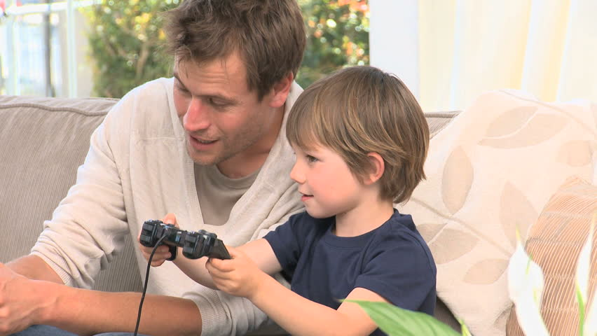 son and dad playing video games stock footage video 1017193 shutterstock. Black Bedroom Furniture Sets. Home Design Ideas