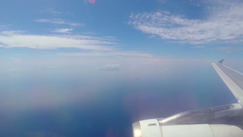 Commercial Airplane flying above blue ocean.