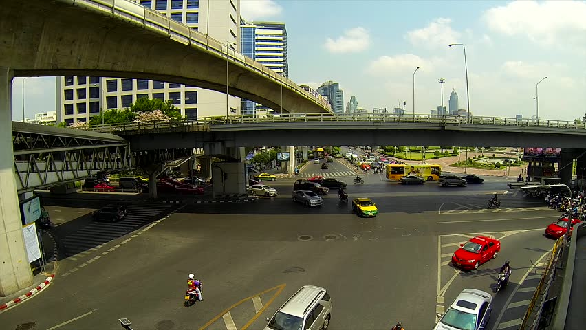 BANGKOK - March 2015: Bangkok's traffic with BTS sky trains passing by. Silom intersection. - HD stock video clip