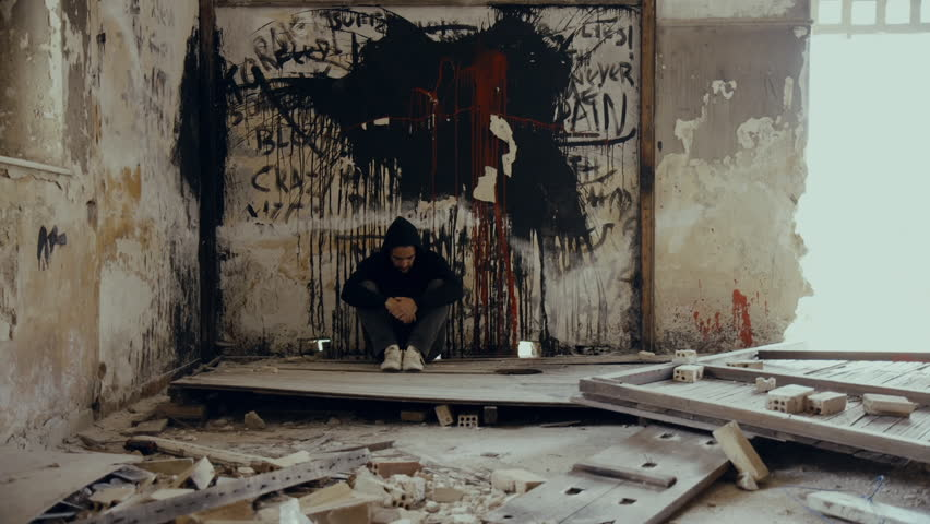 A ,troubled young man wearing a hood in an empty, wrecked,abandoned building, in mental suffering agony and remorse.Slider, tracking motion.