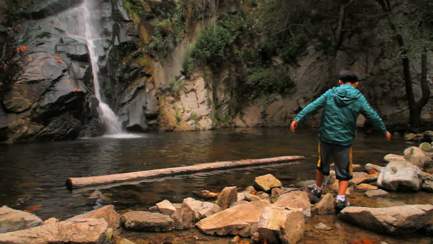 A boy balances on rocks in front of a waterfall. - HD stock footage clip