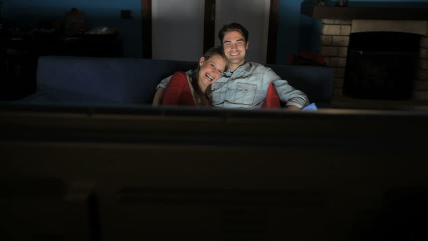couple watching movie on couch while eating popcorn stock