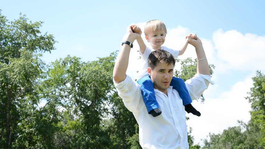 Dad and son playing close to home in the daytime, the son of his father in the neck - HD stock video clip