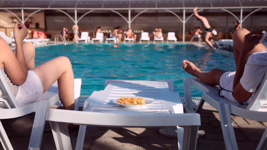 couple enjoying relaxing vacation poolside eating chips
