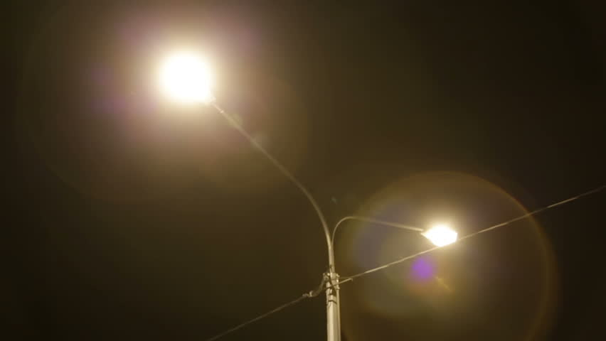 Cars go on night road closeup. Night road is lit by street lamps and cars headlights closeup