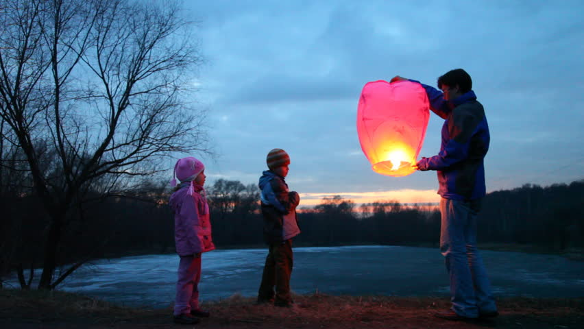 father, son and daughter start glowing pink chinese lantern of winter forest, then look upwards at it