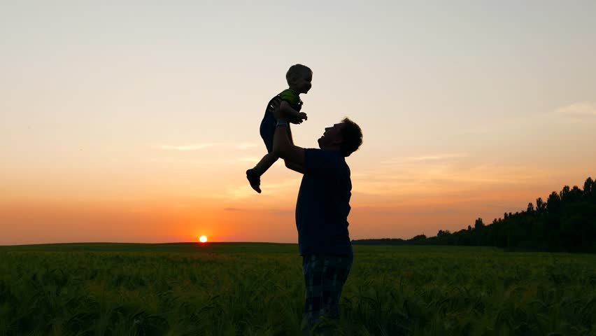 happy joy family, loving father picks up in hands and amuse kid baby toddler at sunset. Childhood dreams and memories. Ecology and environment, fresh air, clean water - 4K stock video clip