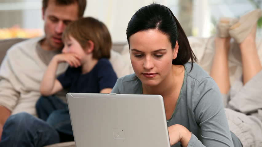 Beautiful woman is on her laptop while her family is on a sofa - HD stock video clip