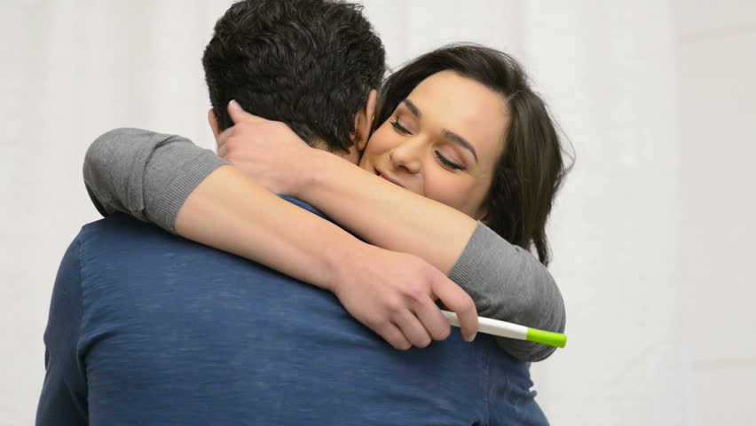 Closeup of happy young woman embracing her boyfriend after positive pregnancy test. Smiling woman embracing man with positive pregnancy test in her hand.