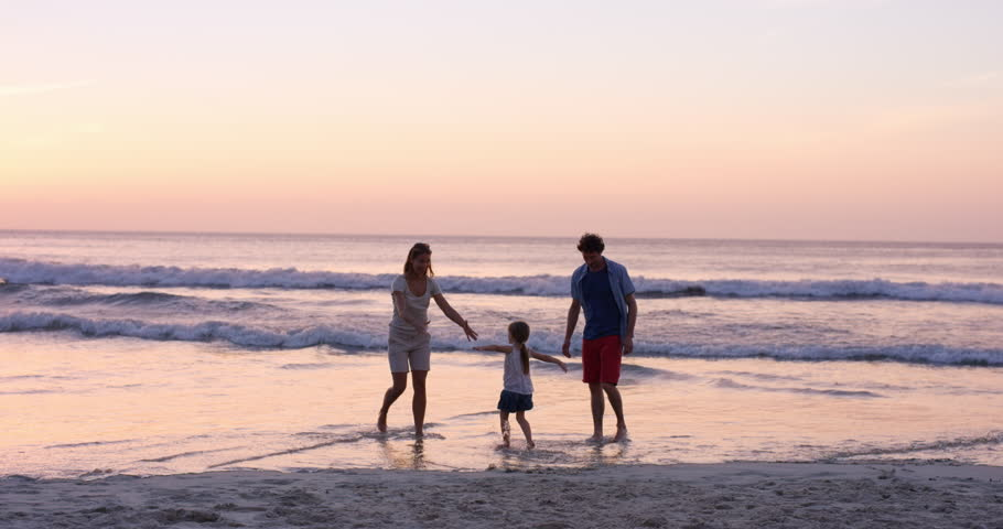 Mother swinging little girl around Happy family on the beach holding hands sat sunset on vacation slow motion RED DRAGON - 4K stock video clip