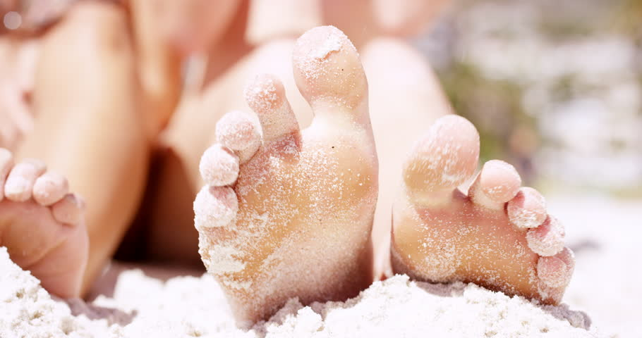 Close up of sandy feet wiggling toes three beautiful young woman sitting on tropical beach vacation