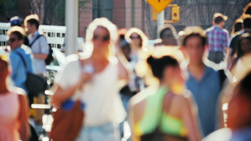 Slow motion of crowded street, people walking, backlit