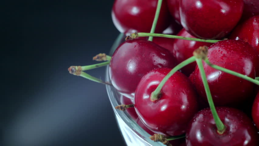 A Group of Ripe Red Cherries in a Beautiful Plate, Rotating on The Table. Close up