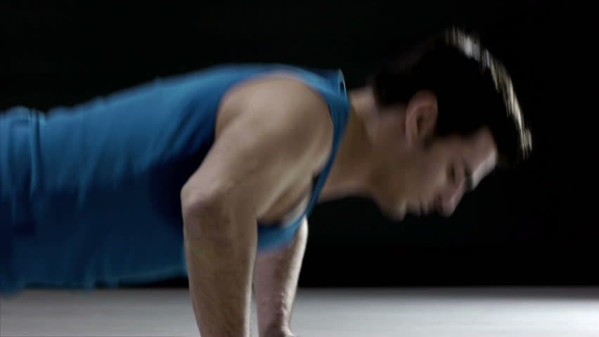Young caucasian male athlete in sportswear doing push ups on black background, people training in gym, man exercising in fitness club. Sequence - HD stock video clip