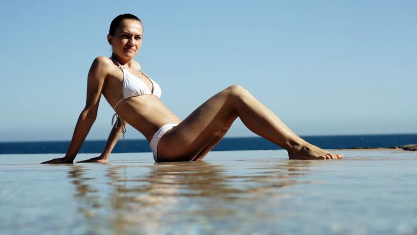 Beautiful sexy woman in white bikini taking sunbath in infinity pool - HD stock footage clip