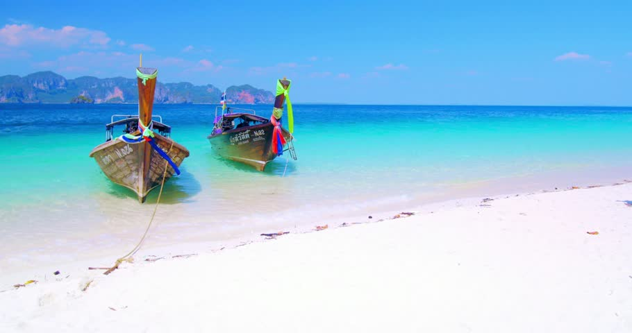 KRABI, THAILAND - 3 MAR 2015: Beautiful background of tropical sandy beach with two wooden thai boats on calm water of crystal clear sea in Thailand near Phuket island. Popular travel destination - 4K stock video clip