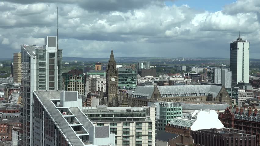 ULTRA HD 4K Timelapse of cloud pass over Manchester rooftop building, crowded town with church tower by day