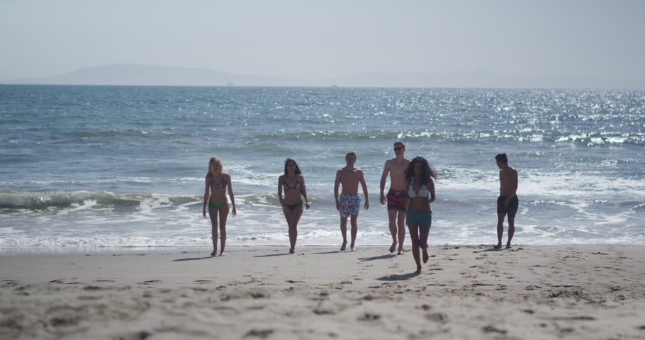Authentic young group of multi ethnic friends strolling from the beach shore