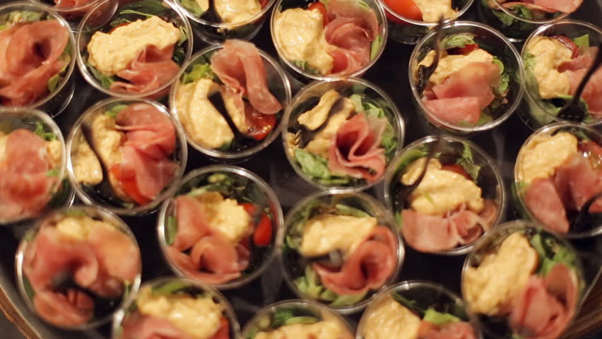 Salad from vegetables, greens and sturgeon in small portions on the catering