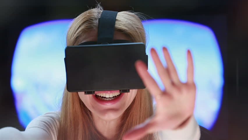 Virtual reality game. Girl with pleasure uses head-mounted display.