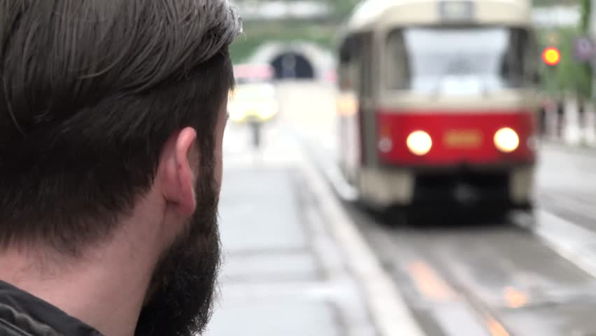 young handsome hipster man look on incoming tram to station in the city - street