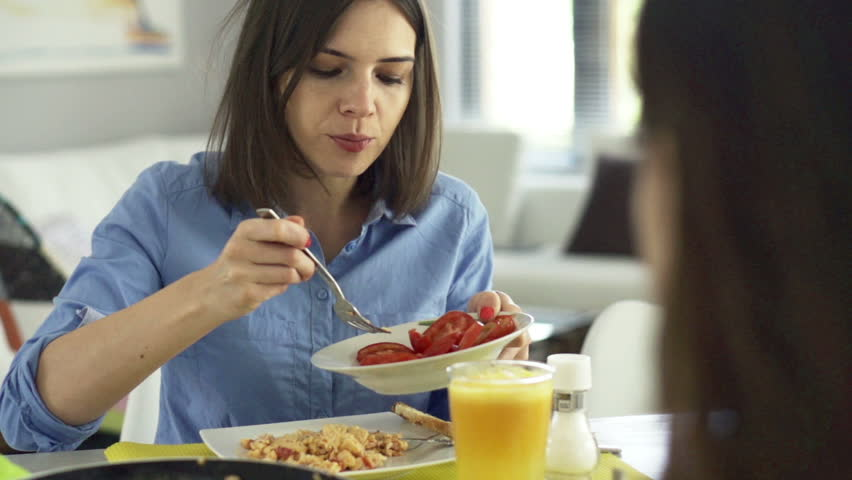 Young woman adding tomato to scrambled eggs by table at home