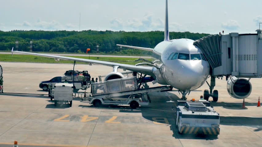 BANGKOK, THAILAND - CIRCA MAY 2015: Timelapse video of baggage handlers offloading luggage from a passenger jet in Bangkok airport, Thailand.