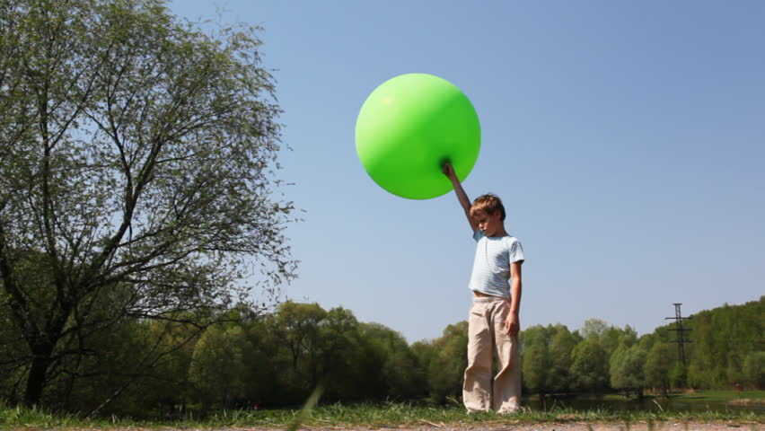 boy holds large inflatable green ball, then carefully goes barefoot on ground and out of frame near forest in summer - HD stock footage clip