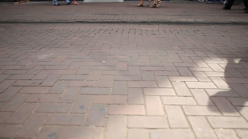 Many walking people in city street, near tramlines