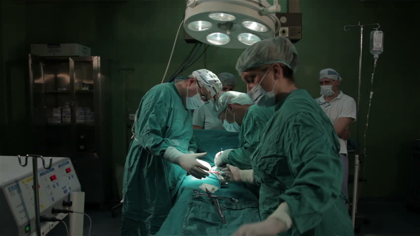 Surgical team operated patient, shallow depth of field. Surgical team performing operation in operating room. doctors making cut with scalpel. Surgery on clinic. Patient lying on the operating table.