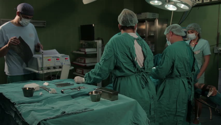 Surgical team performing operation in the operating room. doctors making bloody cut with scalpel. Surgery on the clinic. Patient lying on operating table. Surgeons operate patient in hospital theater.
