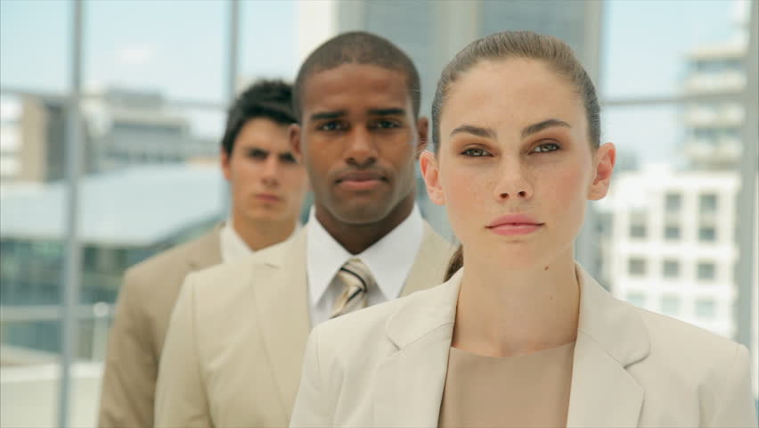 Young confident businesswoman with colleagues. Young business people are in formals. Multi-ethnic male and female professionals are in brightly lit office.