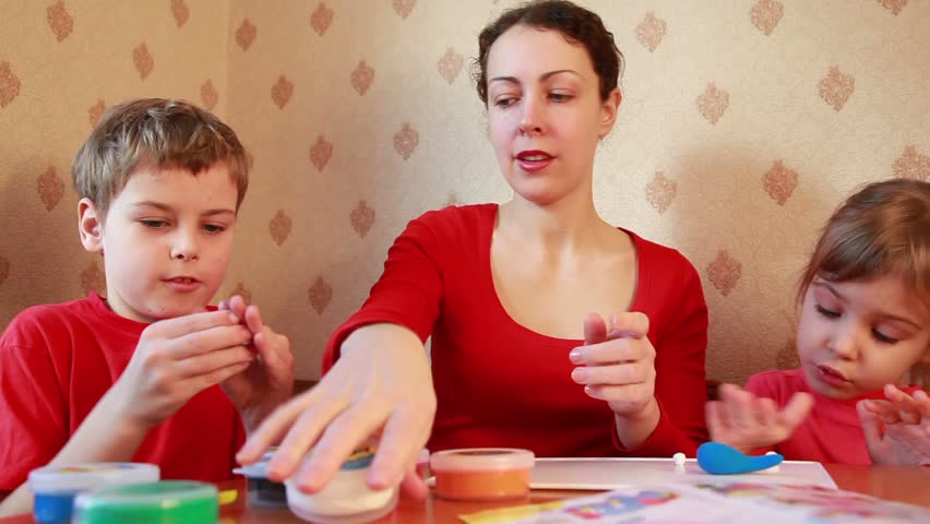 children play with woman on table, sculpt plasticine  - HD stock footage clip