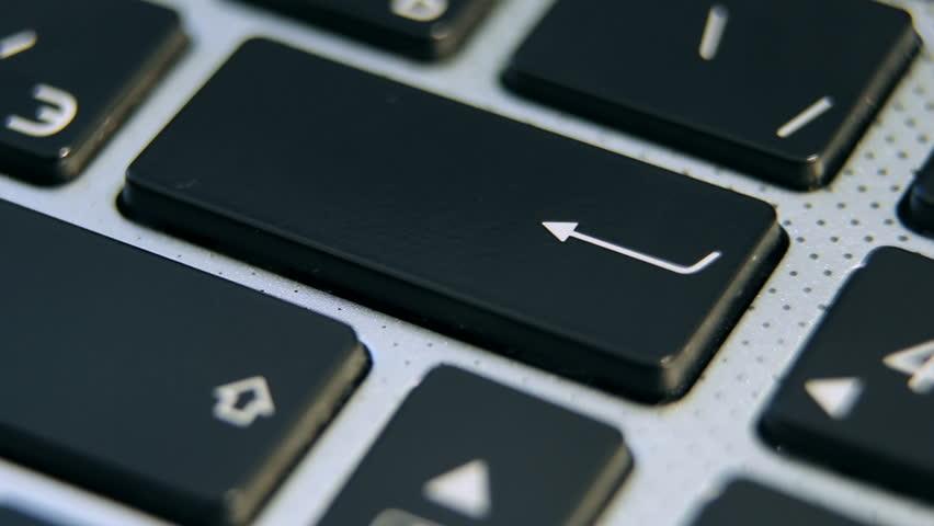 Pressing Enter close-up. Male finger presses Enter on the laptop