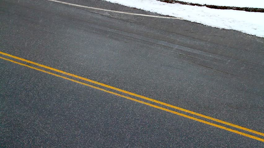 Closeup of yellow double line two lane highway is a snow storm. Slight wind blows snow flakes, snow on the side of road