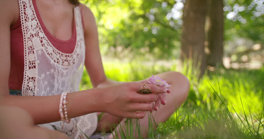 Cropped closeup of a girl's legs with her hands holding a flower while sitting on a lush green grass in a summer park