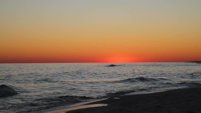 Silhouette of mature man jogging along the seashore at twilight. - HD stock video clip