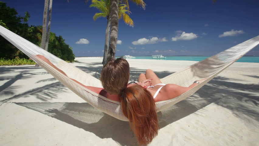 back view of young couple in white relaxing in hammock on sandy beach