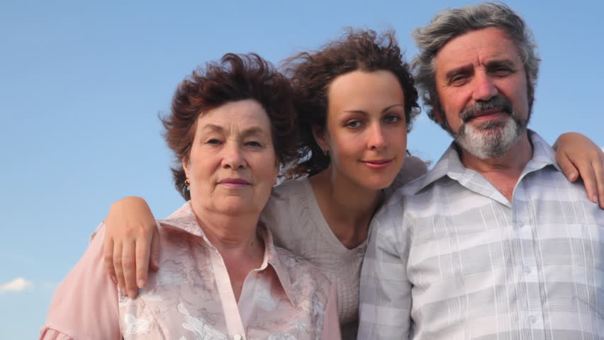 mature couple stands embracing with their adult daughter against sky in summer #1104412