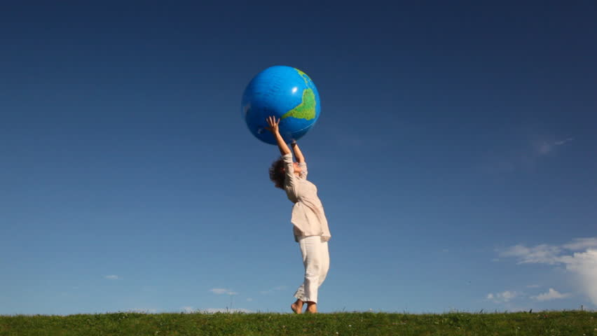 pretty young woman tosses large inflatable earth standing at grass against sky - HD stock video clip