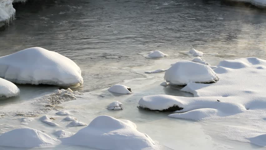Snow and ice covered wilderness lake shoreline. Wind blows toward camera, making small waves. Morning mist rises from water.