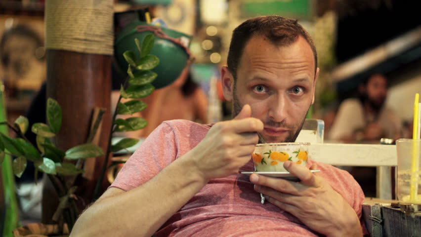 Portrait of funny, young man eating soup sitting in cafe