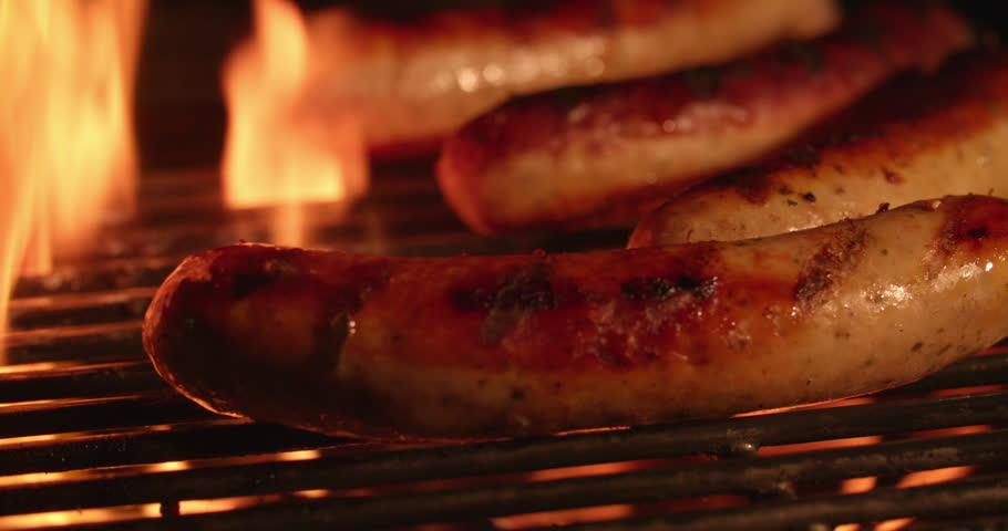 Tasty bratwurst sausages being grilled in the flames of a night time barbecue in Slow Motion