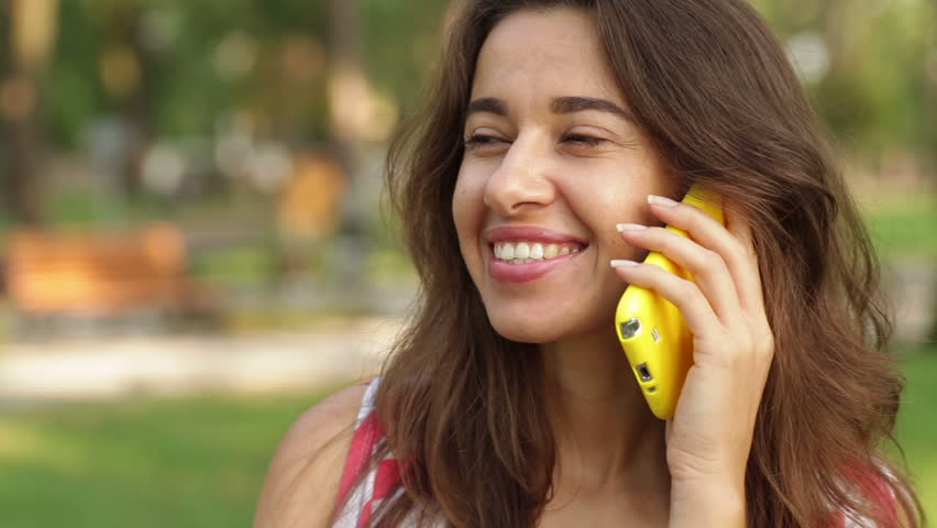 Beautiful woman talking on the phone in the park