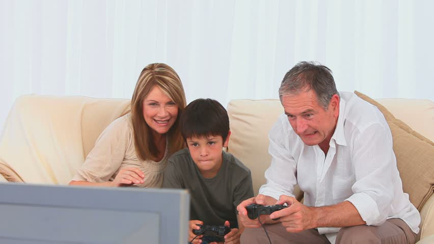 Grandparents playing video games with their grandson in the living room - HD stock video clip