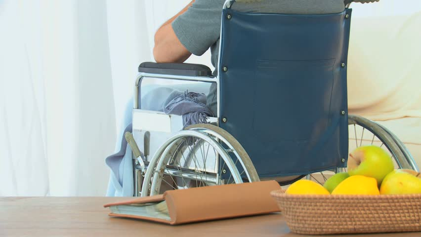 Man in a wheelchair looking through the window at home - HD stock footage clip